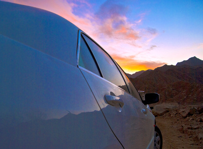 reflection of sunset and mountain on car